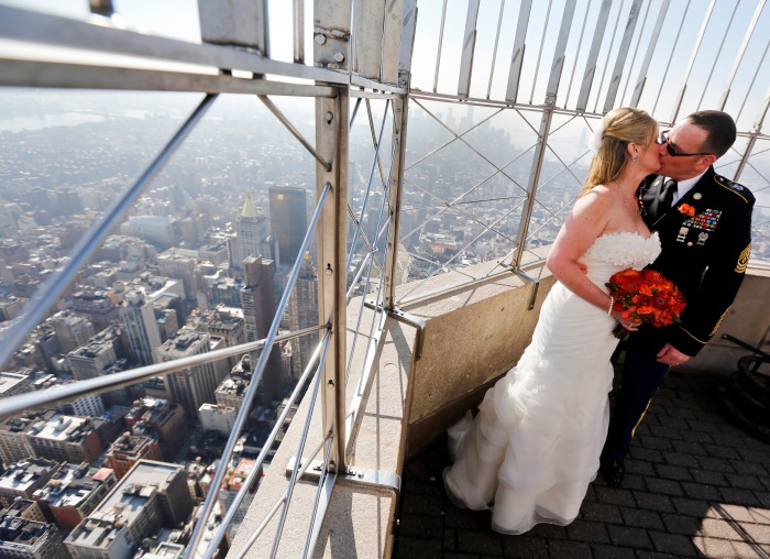 John Kelly and Kari Morey kiss for photographers on the Empire State Building observation deck after their Valentine's Day wedding in New York