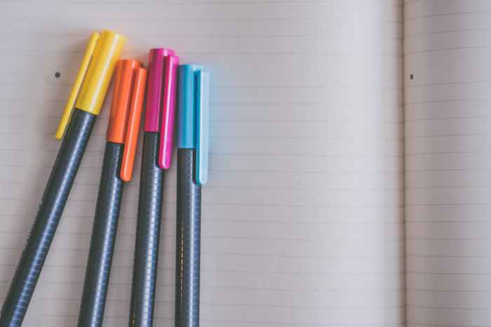 yellow orange pink and blue coloring pens on white notebook