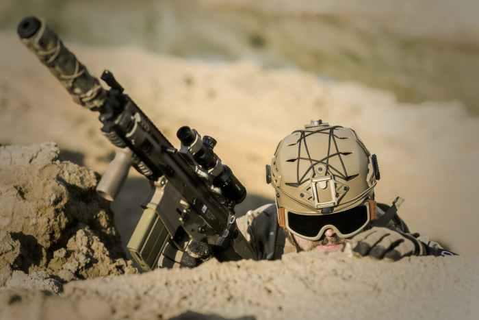 soldier wearing brown helmet holding assault rifle during daytime